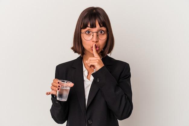 Młoda kobieta biznesu rasy mieszanej trzymając szklankę wody na białym tle dochowując tajemnicy lub prosząc o ciszę.