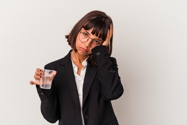 Młoda kobieta biznesu rasy mieszanej trzymając szklankę wody na białym tle jest zszokowana, pamięta ważne spotkanie.