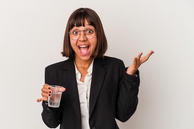 Młoda kobieta biznesu rasy mieszanej trzymając szklankę wody na białym tle otrzymujący miłą niespodziankę, podekscytowany i podnosząc ręce.