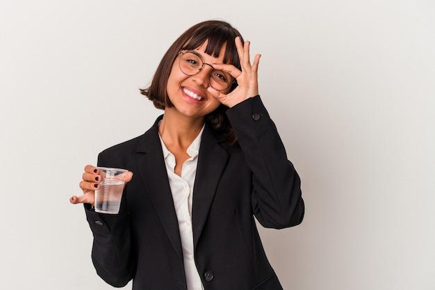 Młoda kobieta biznesu rasy mieszanej trzymając szklankę wody na białym tle podekscytowany utrzymanie ok gest na oko.