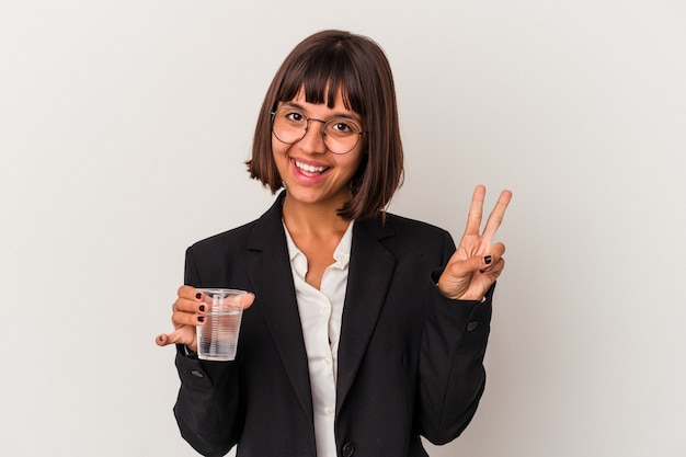Młoda Kobieta Biznesu Rasy Mieszanej Trzymając Szklankę Wody Na Białym Tle Pokazano Numer Dwa Palcami. Premium Zdjęcia