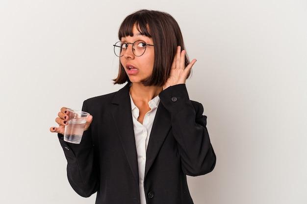 Młoda Kobieta Biznesu Rasy Mieszanej Trzymając Szklankę Wody Na Białym Tle Próbuje Słuchać Plotek. Premium Zdjęcia
