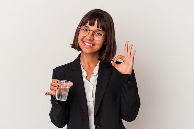 Młoda kobieta biznesu rasy mieszanej trzymając szklankę wody na białym tle wesoły i pewny siebie pokazując ok gest.