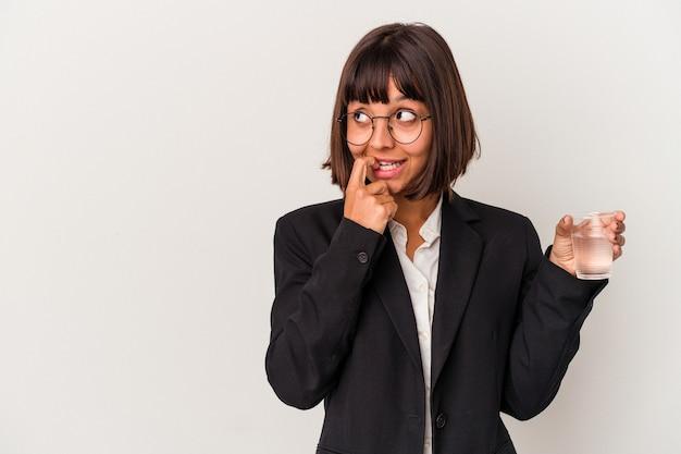Młoda kobieta biznesu rasy mieszanej trzymając szklankę wody na białym tle zrelaksowany myślenie o czymś patrząc na przestrzeni kopii.