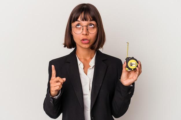 Młoda kobieta biznesu rasy mieszanej, trzymając taśmę mierniczą na białym tle, wskazując do góry z otwartymi ustami.