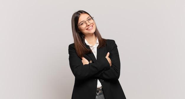 Młoda kobieta biznesu śmiejąca się radośnie ze skrzyżowanymi ramionami, o zrelaksowanej, pozytywnej i zadowolonej pozie