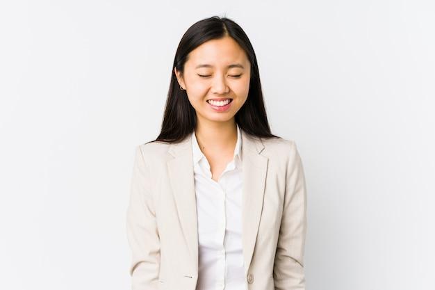 Młoda kobieta biznesu śmieje się i zamyka oczy, czuje się zrelaksowana i szczęśliwa.
