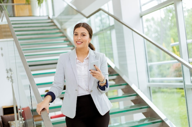 Młoda kobieta biznesu stoi na schodach w biurze i korzystać z telefonu komórkowego