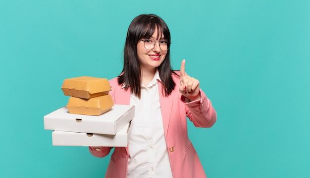 Młoda kobieta biznesu uśmiecha się dumnie i pewnie, triumfalnie tworząc pozę numer jeden, czując się jak lider