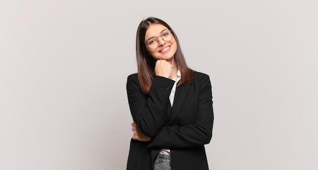 Młoda kobieta biznesu uśmiechnięta, ciesząca się życiem, czująca się szczęśliwa, przyjazna, zadowolona i beztroska z ręką na brodzie