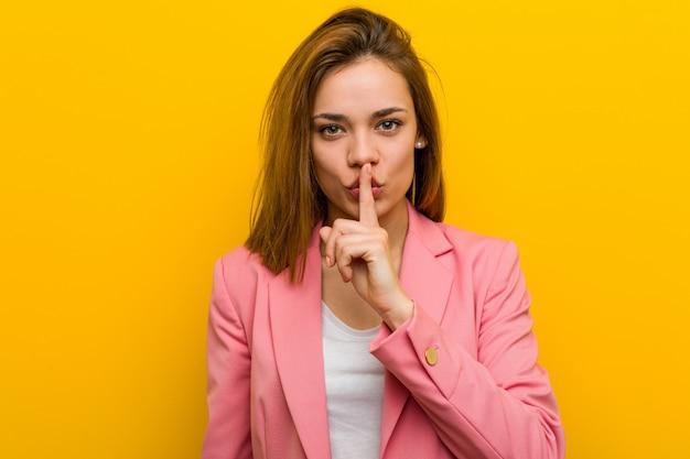 Młoda kobieta biznesu utrzymanie tajemnicy lub prosząc o ciszę.