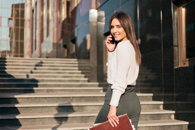 Młoda kobieta biznesu w bluzce i spódnicy rozmawia przez telefon.