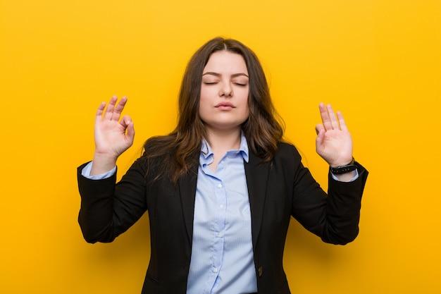 Młoda kobieta biznesu w rozmiarze kaukaskim relaksuje się po ciężkim dniu pracy, wykonuje jogę