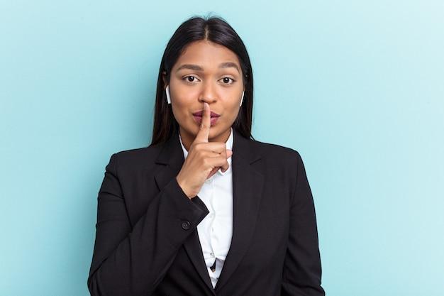 Młoda kobieta biznesu wenezuelskiego na białym tle na niebieskim tle dochowując tajemnicy lub prosząc o ciszę.