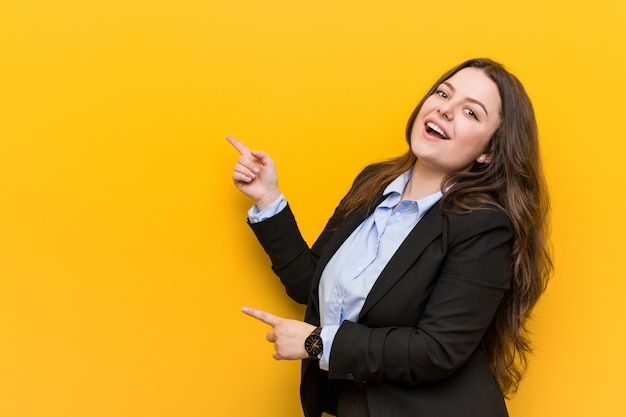 Młoda kobieta biznesu wielkości plus podekscytowana, wskazując palcami z dala