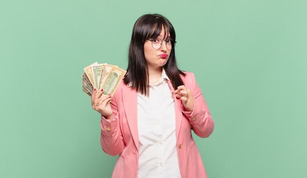 Młoda kobieta biznesu wyglądająca na arogancką, odnoszącą sukcesy, pozytywną i dumną, wskazującą na siebie