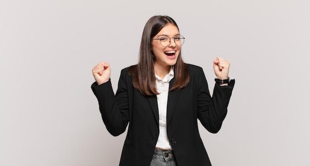 Młoda kobieta biznesu wyglądająca na niezwykle szczęśliwą i zaskoczoną, świętującą sukces, krzyczącą i skaczącą