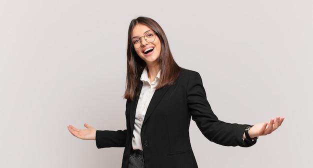 Młoda kobieta biznesu wyglądająca na szczęśliwą, arogancką, dumną i zadowoloną, czującą się jak numer jeden
