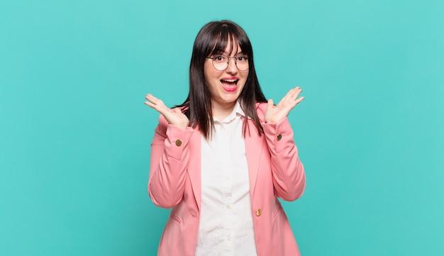 Młoda kobieta biznesu wyglądająca na szczęśliwą i podekscytowaną, zszokowaną nieoczekiwaną niespodzianką z obiema rękami otwartymi obok twarzy