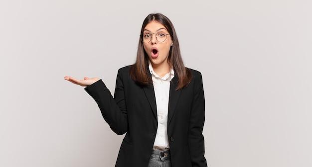 Młoda kobieta biznesu wyglądająca na zaskoczoną i zszokowaną, z opuszczoną szczęką, trzymająca przedmiot z otwartą dłonią z boku