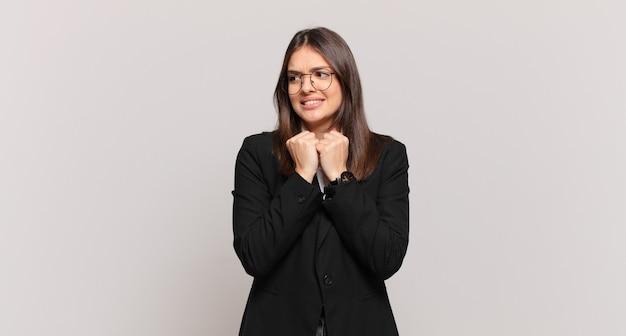 Młoda kobieta biznesu wyglądająca na zmartwioną, zestresowaną, niespokojną i przestraszoną, panikującą i zaciskającą zęby