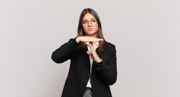 Młoda kobieta biznesu wyglądająca poważnie, surowo, zła i niezadowolona, robiąc znak czasu