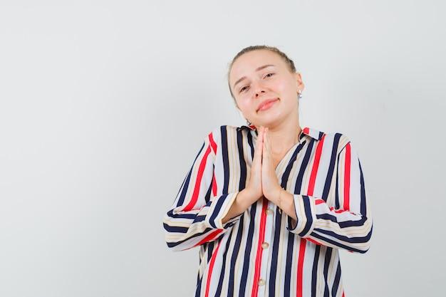 Młoda kobieta błagająca z posłusznym, błagalnym wyrazem twarzy w bluzce w paski i wyglądająca błagalnie