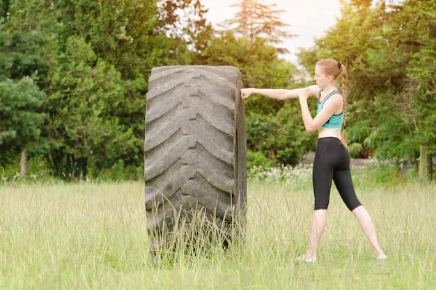 Młoda kobieta boks z oponą. trening