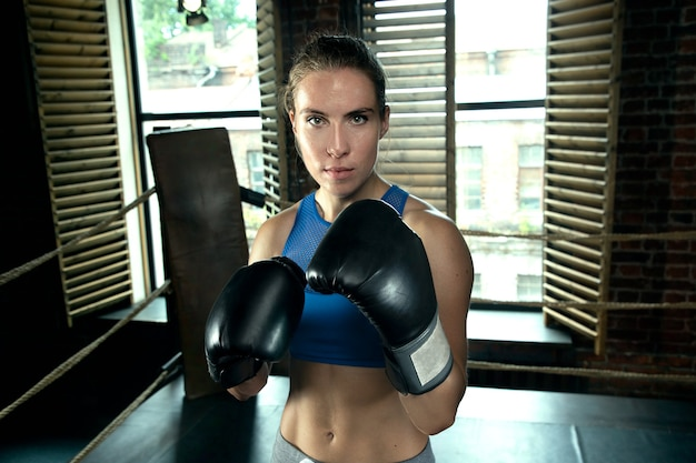 Młoda kobieta bokser pozuje w stojaku
