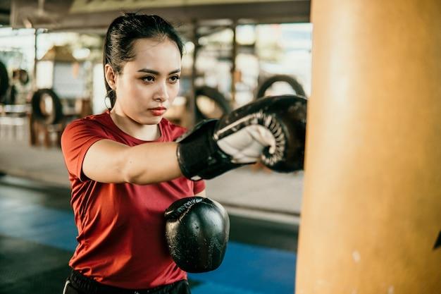 Młoda kobieta bokser robi ćwiczenia uderzając worek treningowy w obozie bokserskim