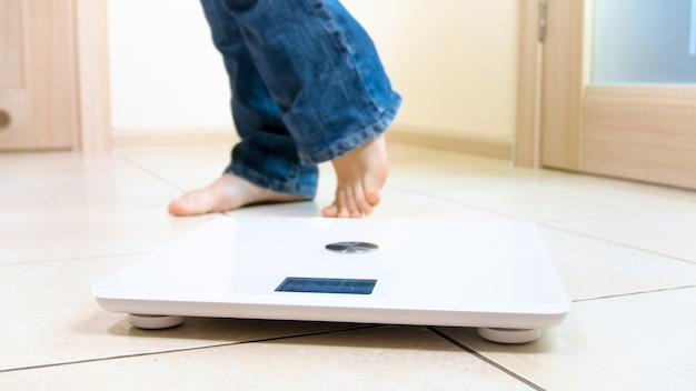 Młoda kobieta boso stojąca na podłodze cyfrowe ciężarki w domu