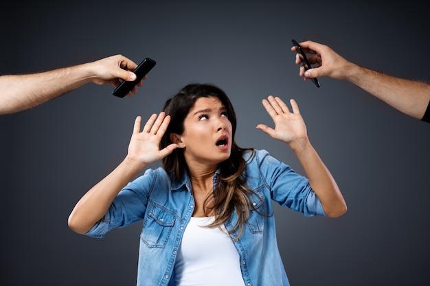 Młoda kobieta broni się przed telefonami. jest zmęczona rozmową telefoniczną.
