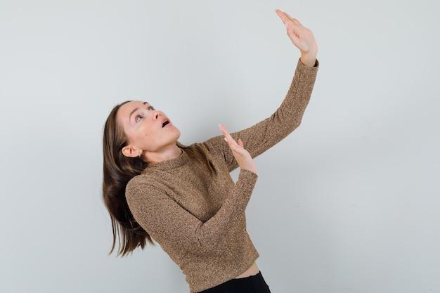 Młoda kobieta, broniąca się przed czymś w złotej bluzce i wyglądająca na przestraszoną. .