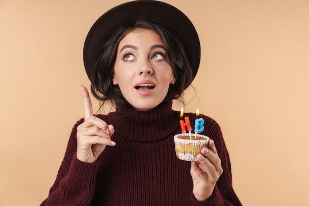 Młoda kobieta brunetka myślenia na białym tle nad beżową ścianą trzyma ciastko z okazji urodzin świeczki wskazując.