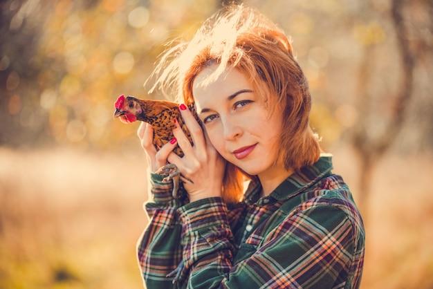 Młoda kobieta brunetka trzyma koguta w dłoniach, święta wielkanocne lub martindiena na łotwie