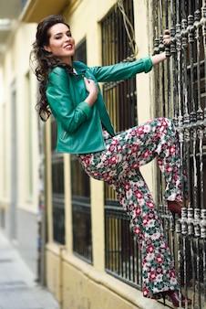 Młoda kobieta brunetka uśmiecha się w tle miejskich.