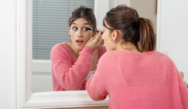 Młoda kobieta brunetka wprowadzenie makijażu w lustrze