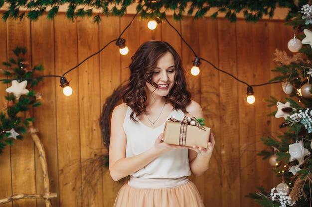 Młoda kobieta brunetka z prezentem. nowy rok koncepcji bożego narodzenia