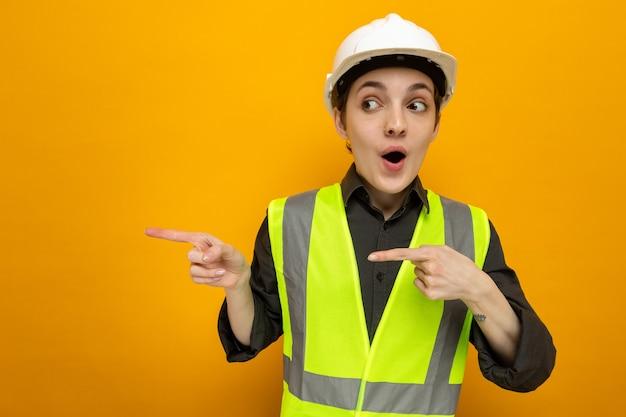 Młoda kobieta budowlana w kamizelce budowlanej i kasku ochronnym, patrząc z zaskoczenia, wskazując palcami wskazującymi w bok, stojąc na pomarańczowo