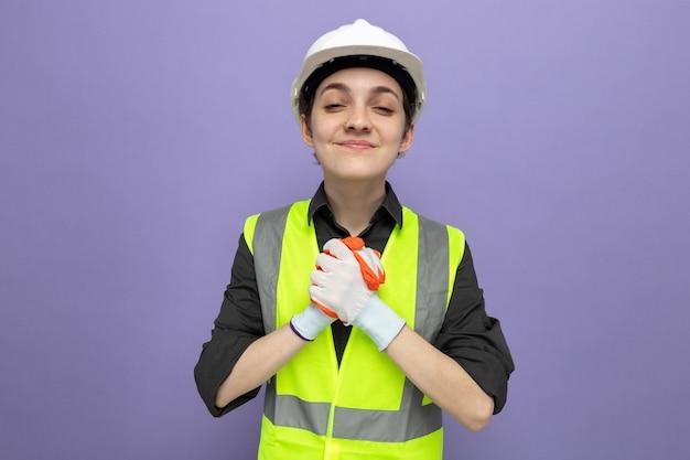 Młoda kobieta budowlana w kamizelce budowlanej i kasku ochronnym w gumowych rękawiczkach, patrząc z przodu, uśmiechając się radośnie trzymając się za ręce, stojąc nad fioletową ścianą