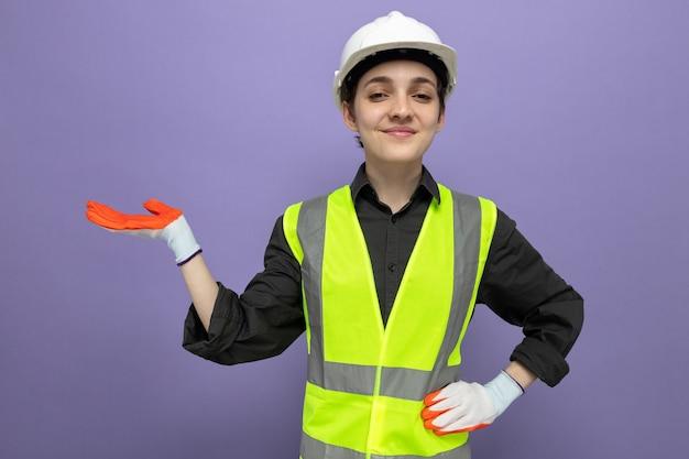 Młoda kobieta budowlana w kamizelce budowlanej i kasku ochronnym w gumowych rękawiczkach uśmiecha się pewnie prezentując przestrzeń z ramieniem dłoni stojącym na niebiesko
