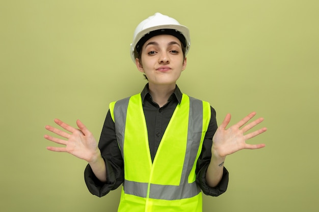 Młoda kobieta budowlana w kamizelce budowlanej i kasku ochronnym zdezorientowana rozkładając ręce na boki, stojąc na zielono