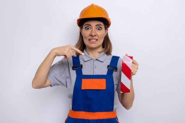Młoda kobieta budowlana w mundurze budowlanym i kasku ochronnym, trzymająca taśmę klejącą wskazującą palcem wskazującym na nią, patrząc zdezorientowaną, stojąc nad białą ścianą