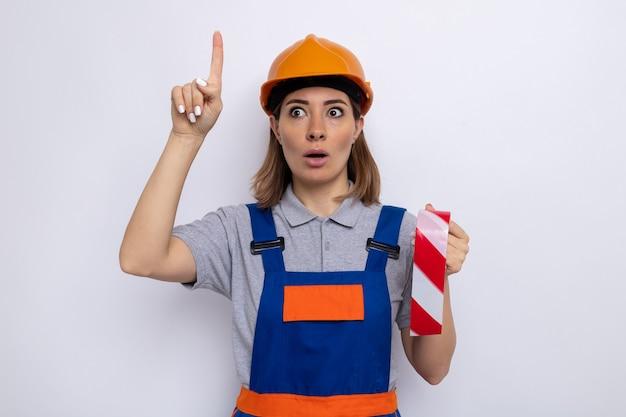 Młoda kobieta budowlana w mundurze budowlanym i kasku ochronnym, trzymająca taśmę samoprzylepną, patrząc na zdziwioną i zmartwioną pokazując palec wskazujący