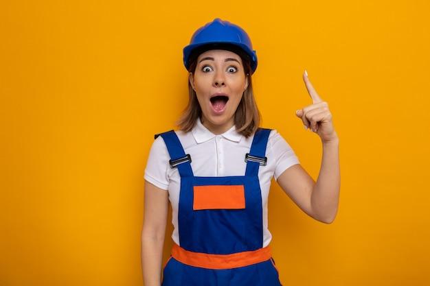 Młoda kobieta budowlana w mundurze budowlanym i kasku ochronnym wygląda na zdziwioną i zaskoczoną pokazując palec wskazujący, mający świetny pomysł