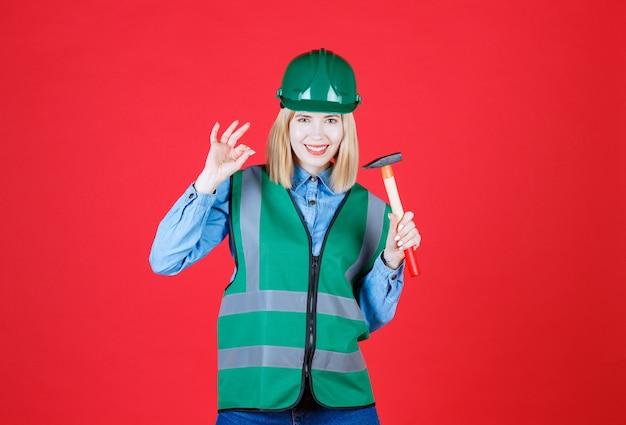 Młoda kobieta budowniczy na sobie zielony mundur i hełm trzymając młotek na białym tle czerwony