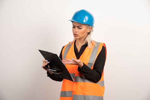 Młoda kobieta budowniczy patrząc w schowku. wysokiej jakości zdjęcie