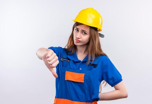 Młoda kobieta budowniczy pracownik w mundurze budowlanym i hełmie ochronnym, patrząc niezadowolony, pokazując kciuk w dół stojąc na białej ścianie
