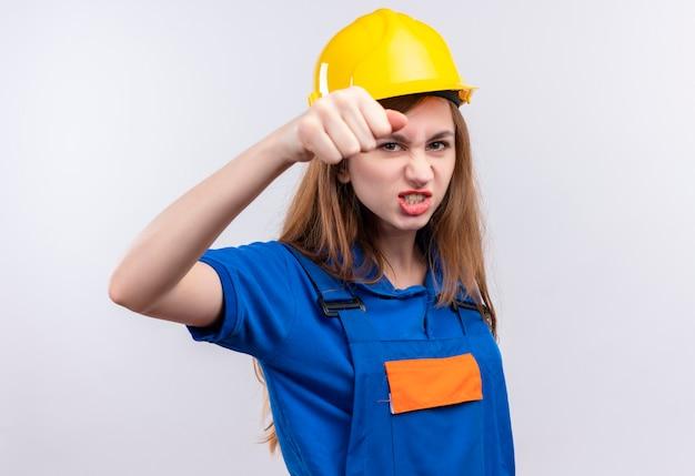 Młoda kobieta budowniczy pracownik w mundurze budowlanym i kasku, zaciskając pięść z przodu