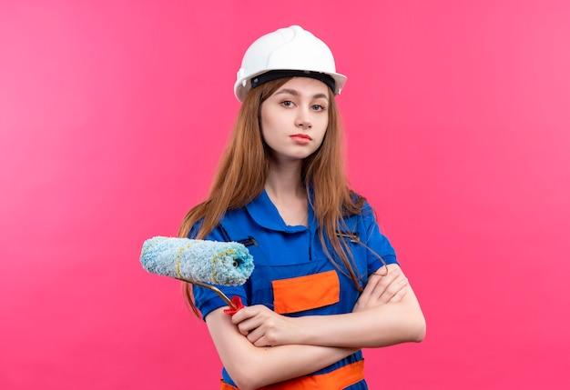 Młoda kobieta budowniczy pracownik w mundurze budowy i hełm ochronny stojący z rękami skrzyżowanymi trzymając wałek do malowania patrząc pewnie na różowej ścianie